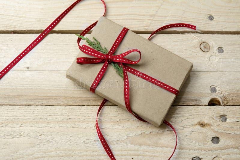 Prezenta pudełko, zawijający w przetwarzającym papierze i czerwonym łęku na drewnianym backgrou fotografia stock