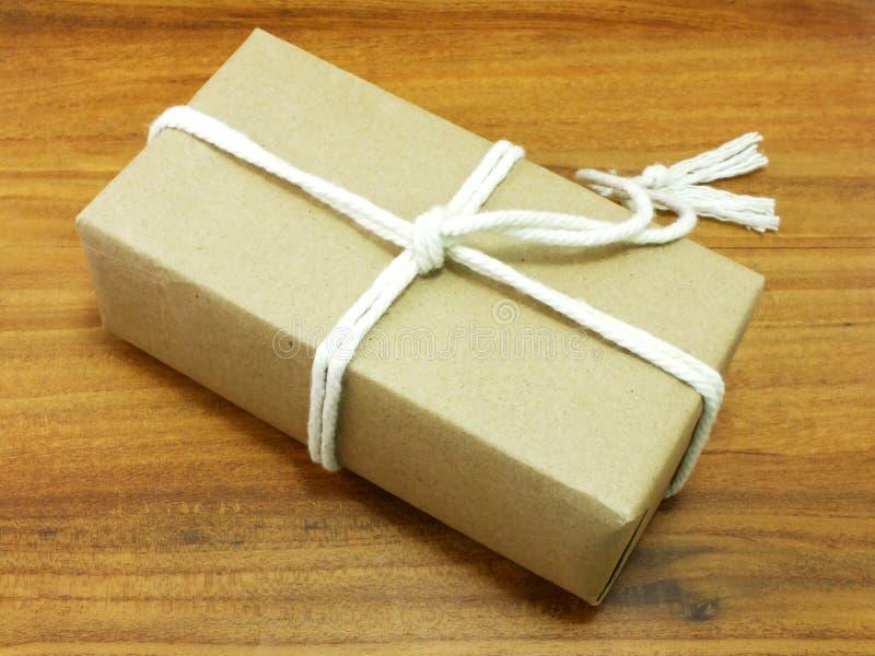 Prezenta pudełko zawijający w przetwarzającym papierze z białą arkaną obraz stock