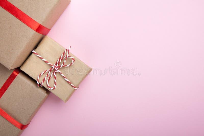 Prezenty od przetwarzającego papieru, dekorującego z czerwonymi faborkami na różowym tle kosmos kopii zdjęcie stock