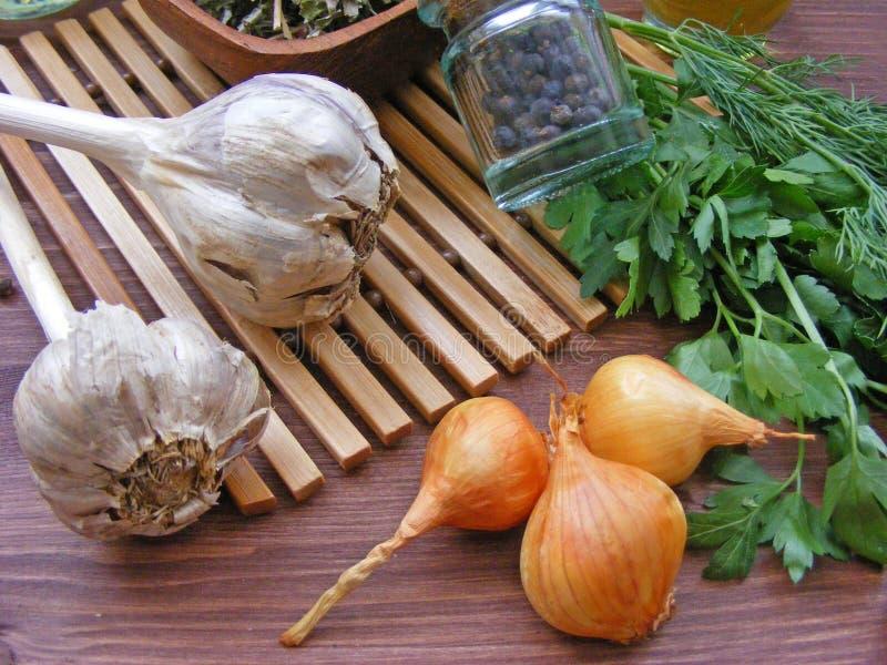 Prezzemolo fresco, cipolla rossa, aglio, bacche asciutte per cucina rustica, fine sulla vista fotografia stock