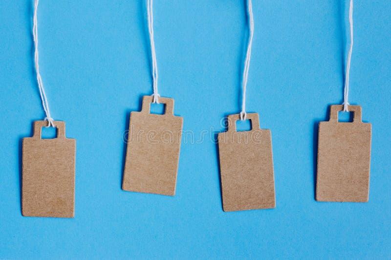Prezzi da pagare marroni in bianco del cartone, etichetta di vendita, etichetta del regalo, etichetta di indirizzo su fondo blu immagini stock libere da diritti