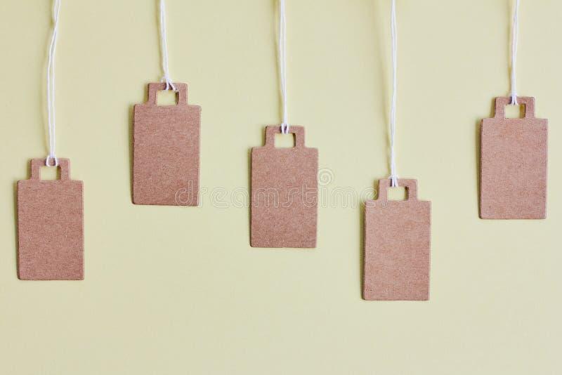 Prezzi da pagare marroni in bianco del cartone, etichetta di vendita, etichetta del regalo, etichetta di indirizzo su fondo giall fotografia stock