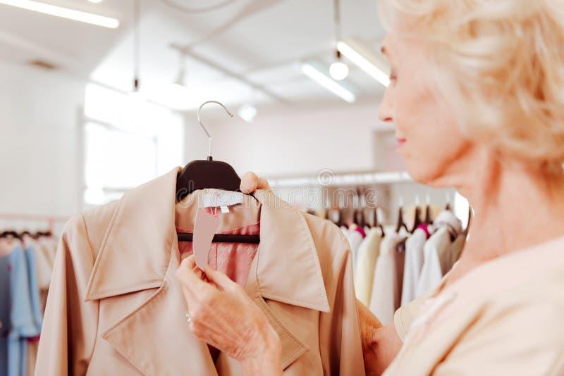Prezzo da pagare alla moda della tenuta della donna del cappotto mentre comperando immagini stock