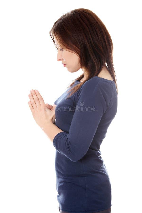 Prière âgée moyenne de femme photo libre de droits
