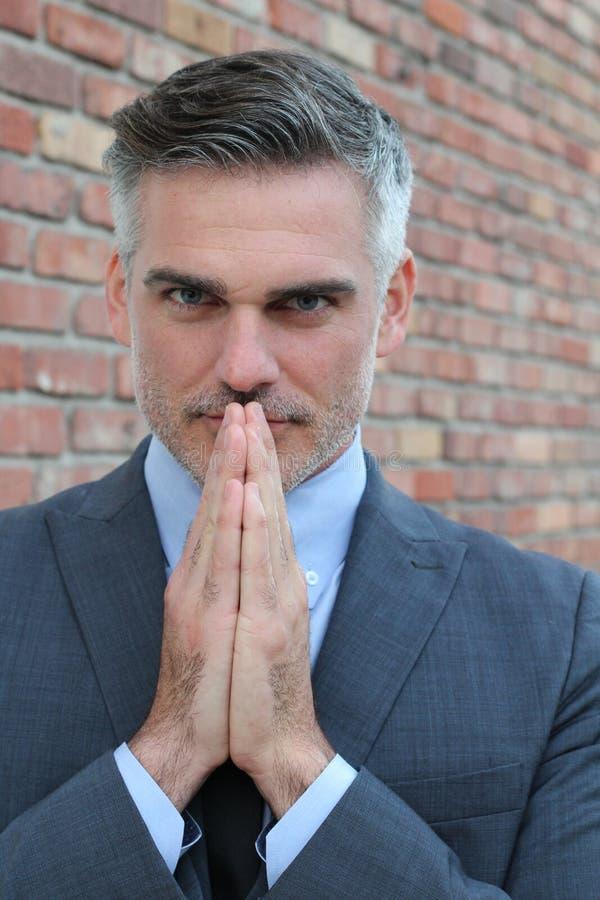 Prière d'homme d'affaires L'homme mûr réfléchi dans le formalwear tenant des mains a étreint près du visage et tout en se tenant  image stock