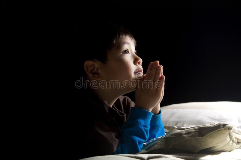 Prière de l'heure du coucher du jeune garçon. photos libres de droits