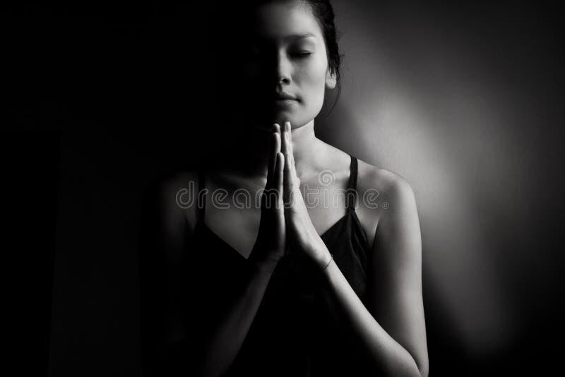 Prière femelle sur l'obscurité photographie stock