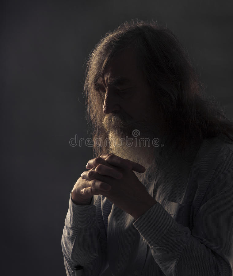 Prière supérieure, vieil homme priant avec les mains pliées dans l'obscurité photographie stock libre de droits