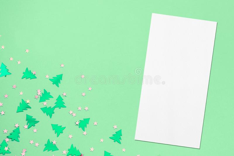Price-list or menu mockup on christmas mint background. Empty price-list or menu mockup with soft shadows lying diagonally on mint background with metallic foil royalty free stock image