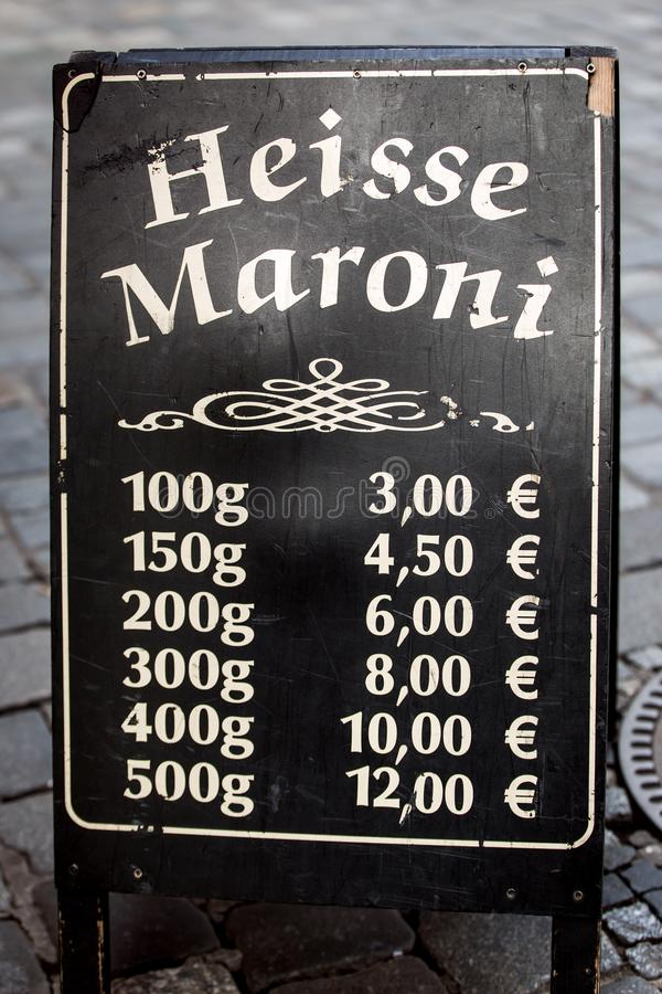 Price list sign for hot sweet chestnuts in germany. German words stock photo