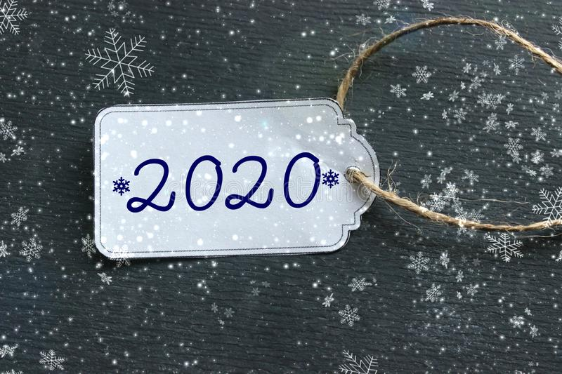 The price tag with the numbers 2020, the white tag against the black wood. The concept of the new 2020. New year background. Price tag, gift tag, sale tag stock photo