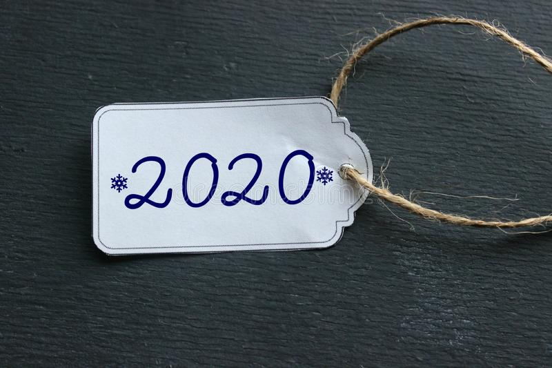 The price tag with the numbers 2020, the white tag against the black wood. The concept of the new 2020. New year background. Price tag, gift tag, sale tag royalty free stock image