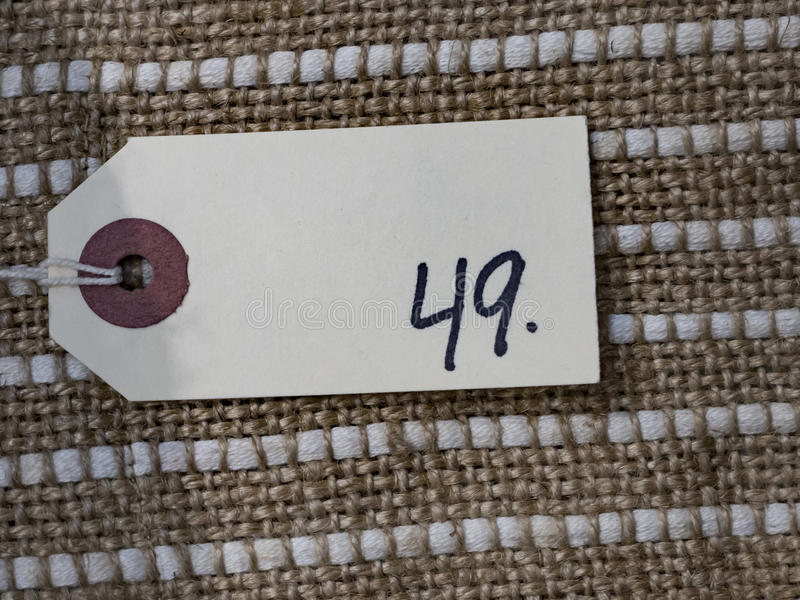 Price tag 49. A white cardboard price tag with 49 written on it with a black marker. The price tag is laying on a textile background royalty free stock photos