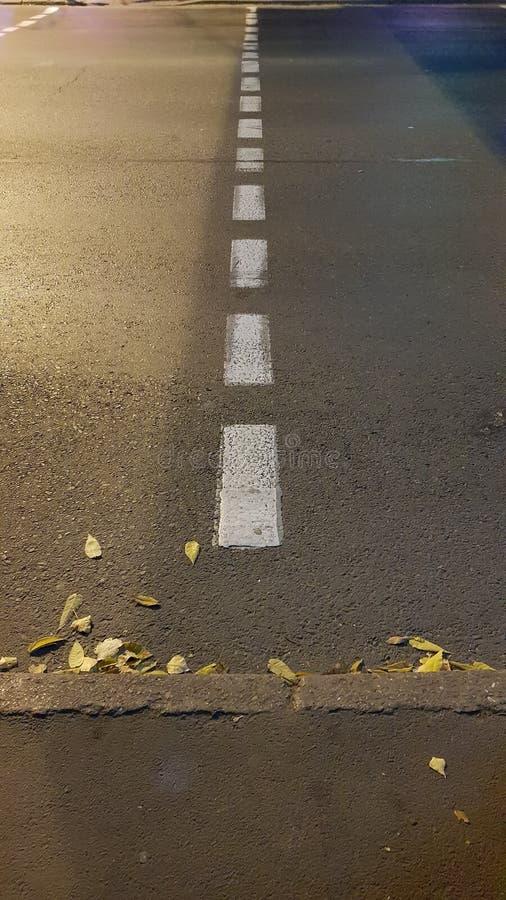 Prickig linje av vägteckning på grov asfaltyttersida royaltyfria foton