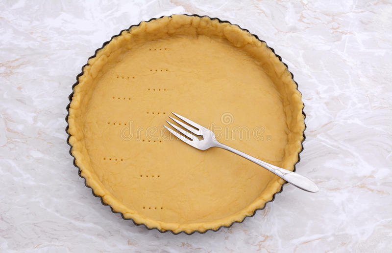 Pricking shortcrust pastry case with a metal fork stock photos