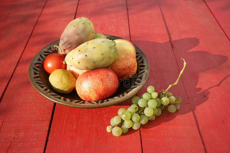 Prickly pears fruits, apples, pears, grapes on red table stock photo