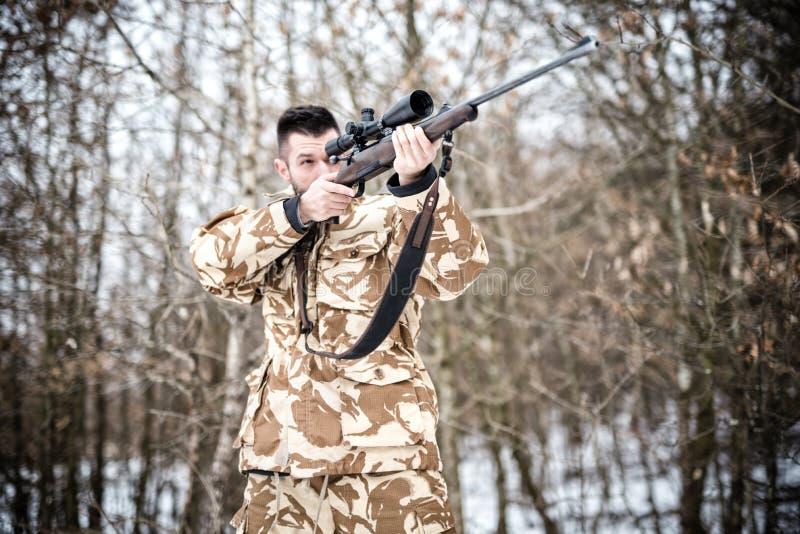 Prickskytt med vapnet som är klart för strid eller jakt i skogen royaltyfria bilder