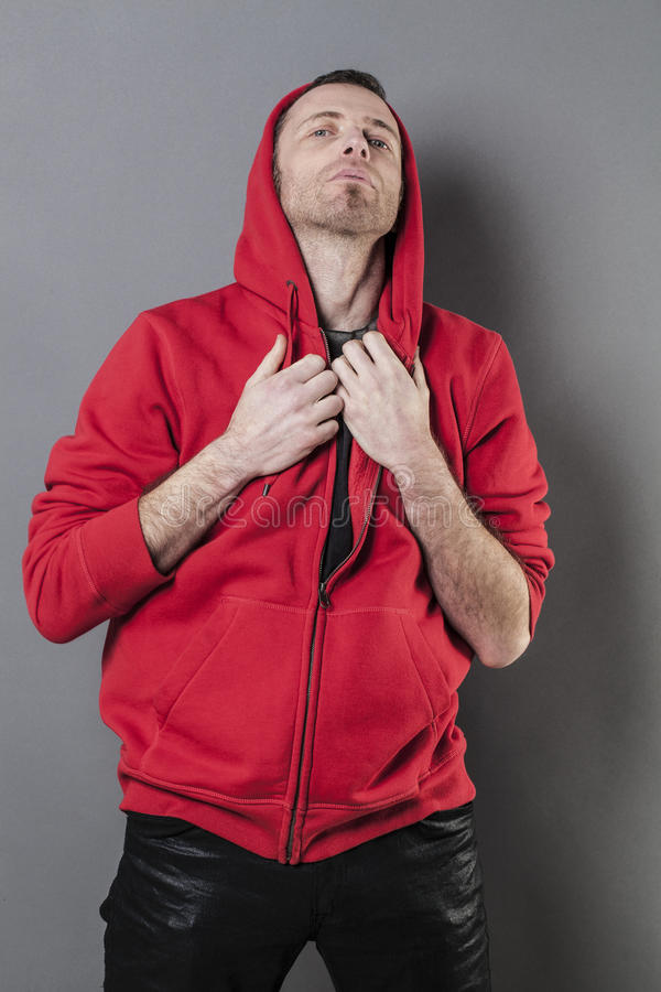 Pride and arrogance for outraged 40s man. Pride and arrogance - outraged 40s man wearing a red hoodie acting offended for confrontation and attitude,gray stock photos
