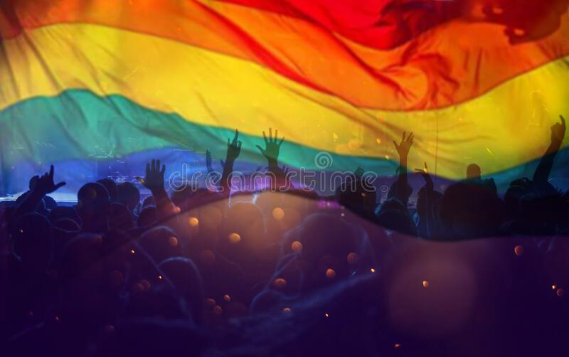 Colorful LGBT flag blows in the breez over crowd stock photography