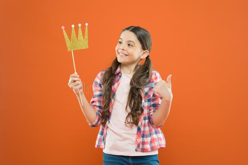 That pride of hers. Cute small girl holding prop crown with pride on orange background. Adorable little princess feeling royalty free stock images