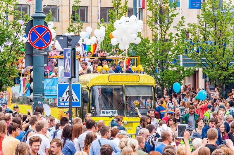 Pride parade event in action. Crowd of watchers surrounding yellow open top bus decorated with white balloons full of royalty free stock photography
