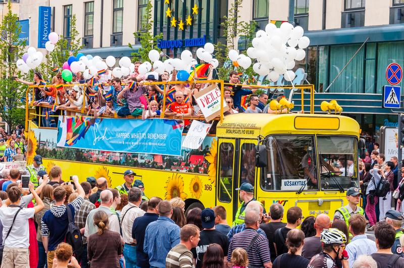 Pride parade event in action. Crowd of watchers surrounding yellow open top bus decorated with white balloons full of stock images
