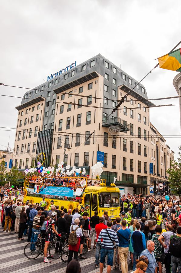 Pride parade event in action. Crowd of watchers surrounding yellow open top bus decorated with white balloons full of stock photo