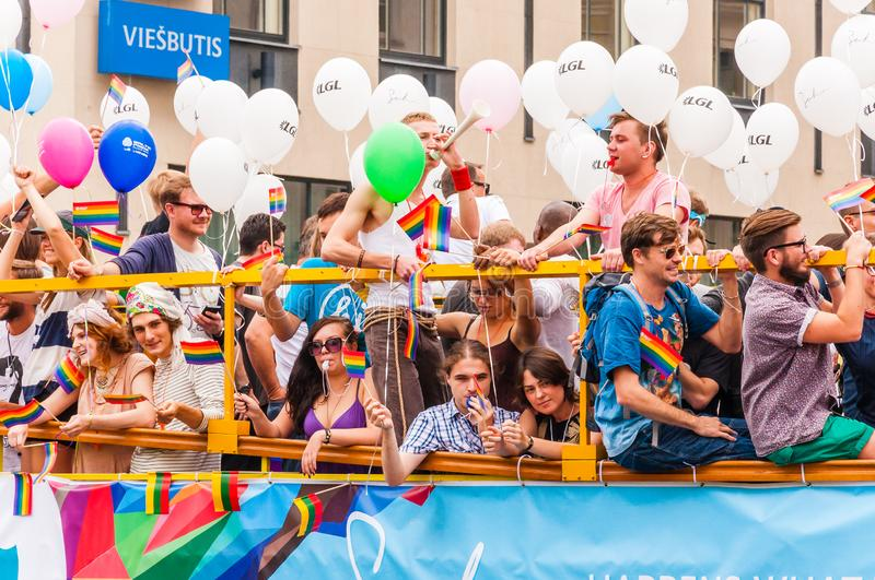 Pride parade event in action. Proud and happy people demonstrators standing on yellow open top bus decorated with vibrant and royalty free stock images
