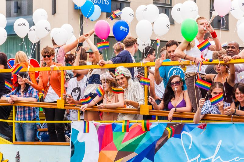 Pride parade event in action. Proud and happy people demonstrators standing on yellow open top bus decorated with vibrant and stock image