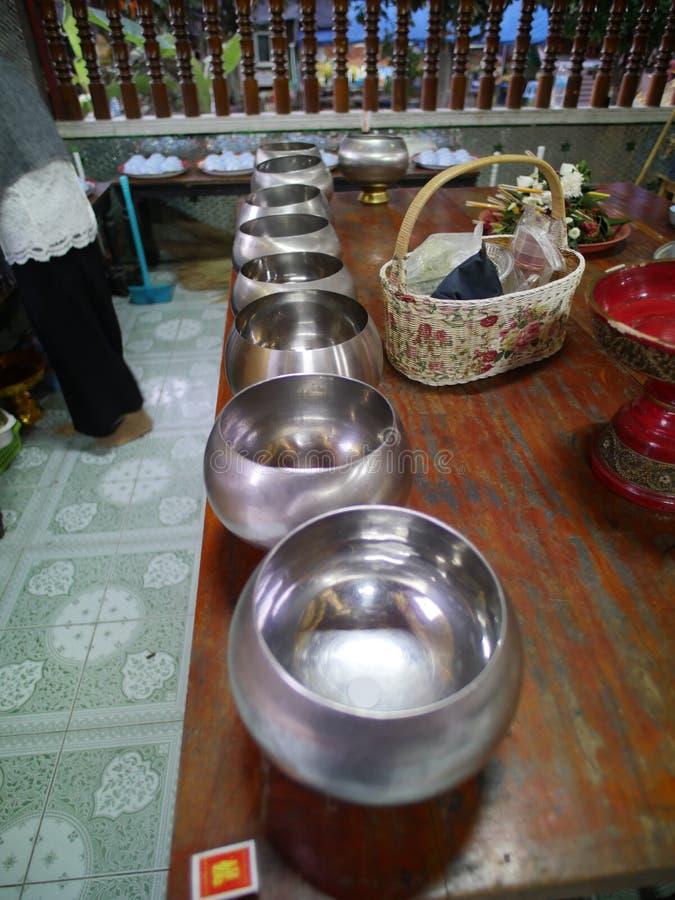 Prier des cuvettes ou des cuvettes d'aumône en Thaïlande images libres de droits