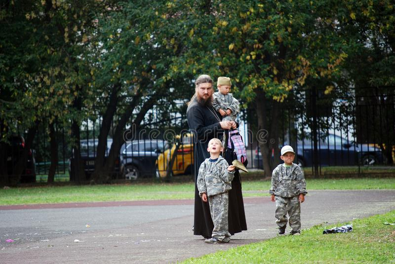 The priest in a cassock costs at the playground with the little sons dressed in a clothes camouflage. stock images