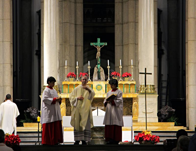 Father and altar boys on the altar of the cathedral. stock photography