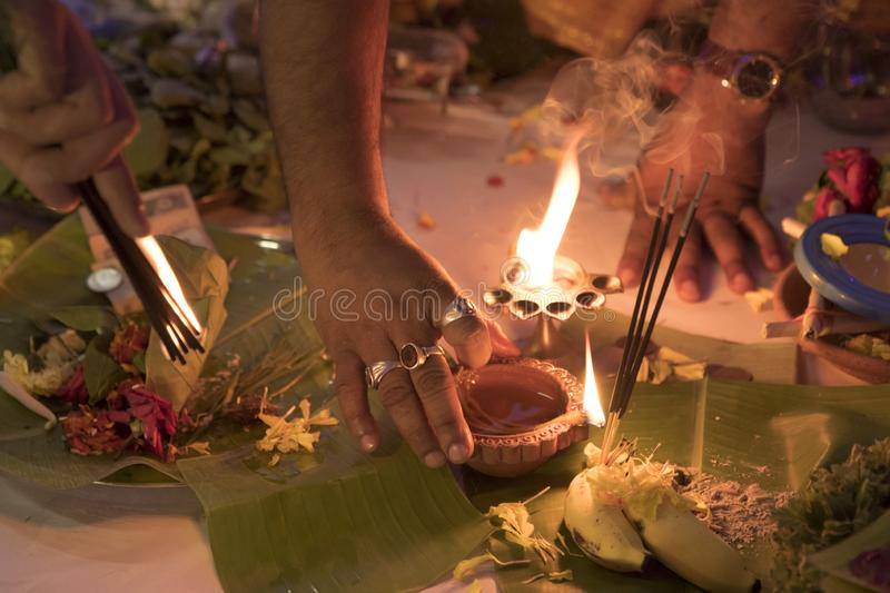 Priest doing rituals in Hindu puja. Priest is busy doing certain rituals during a hindu puja worship/prayer. Fire here signifies the sacred flavour of any such royalty free stock photo
