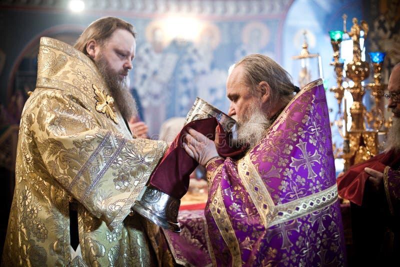 The priest drinks wine stock photo