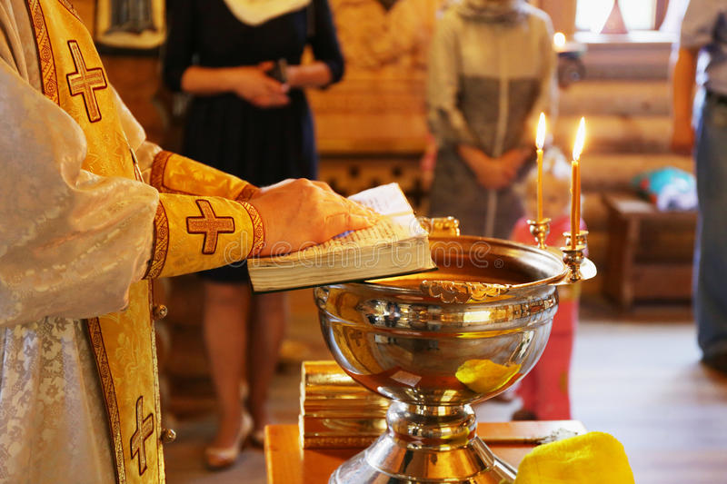 Priest about the font. Priest reads the prayer near the baptismal font during the baptism (baptism, christening, Epiphany stock photos