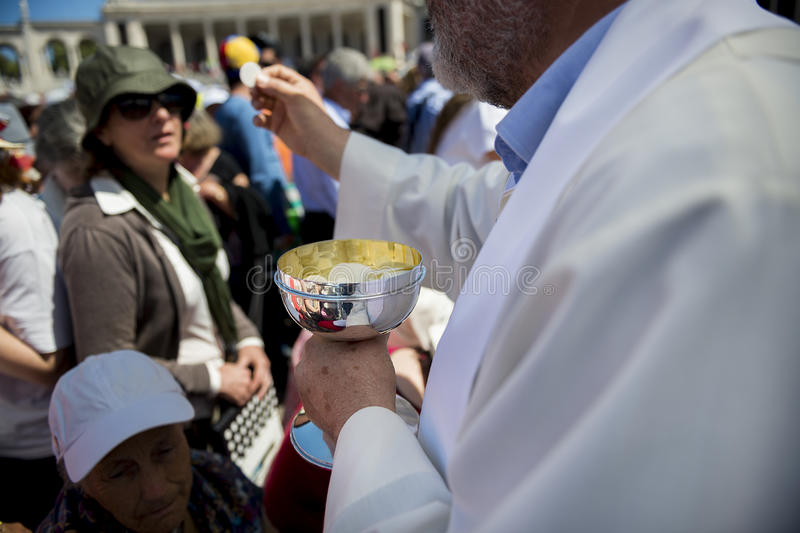 Priest holding a ciborium with sacramental bread at the Sanctuary of Fatima during the celebrations of the apparition of the Virgi. Fatima, Portugal - May 13 stock images