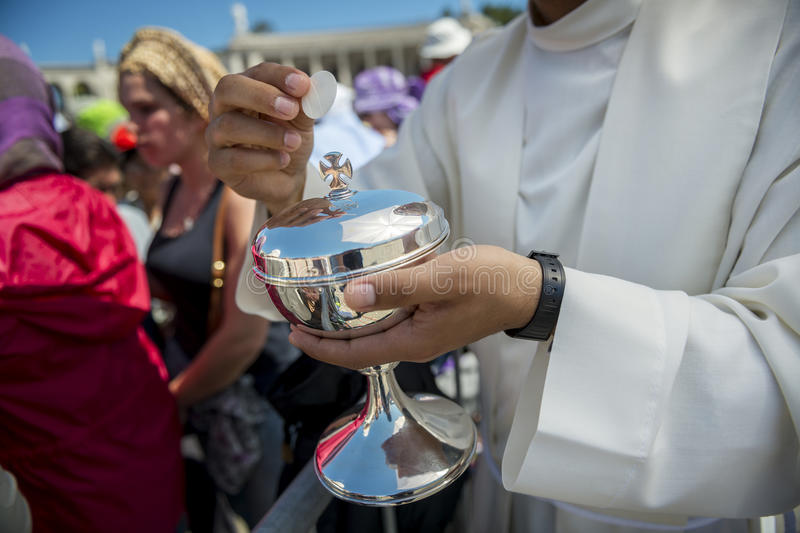 Priest holding a ciborium with sacramental bread at the Sanctuary of Fatima during the celebrations of the apparition of the Virgi. Fatima, Portugal - May 13 stock image