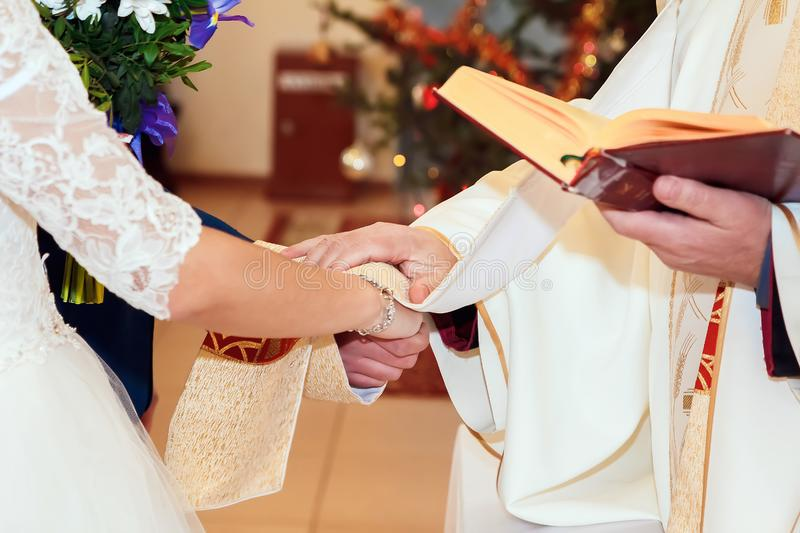 Priest holding hands of stylish bride and elegant groom at catholic wedding ceremony at church stock photo