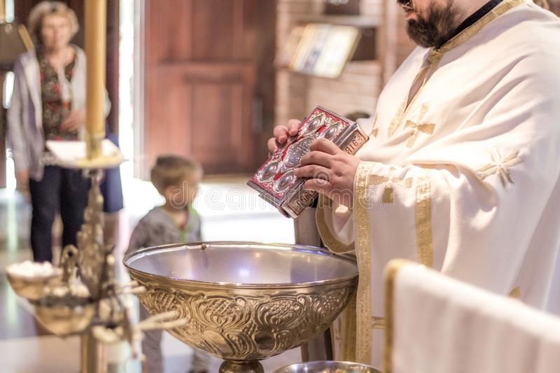 Priest holding Holy Bible above the Holy water on the ceremony royalty free stock photography