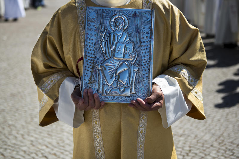 Priest holding a Holy Bible at the Sanctuary of Fatima during the celebrations of the apparition of the Virgin Mary in Fatima, Por. Fatima, Portugal - May 13 stock photo