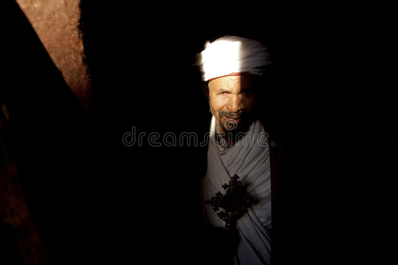 A Priest in Lalibela. A Priest looking between the stones of a monolithic church, Lalibela royalty free stock photos