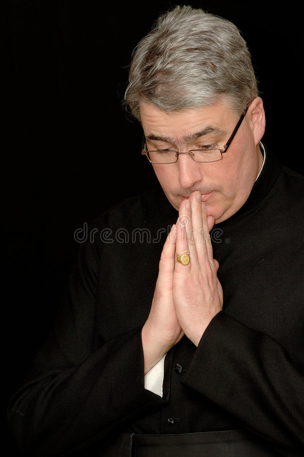 Priest in prayers. Portrait of a catholic priest saying his prayers, black background image royalty free stock images