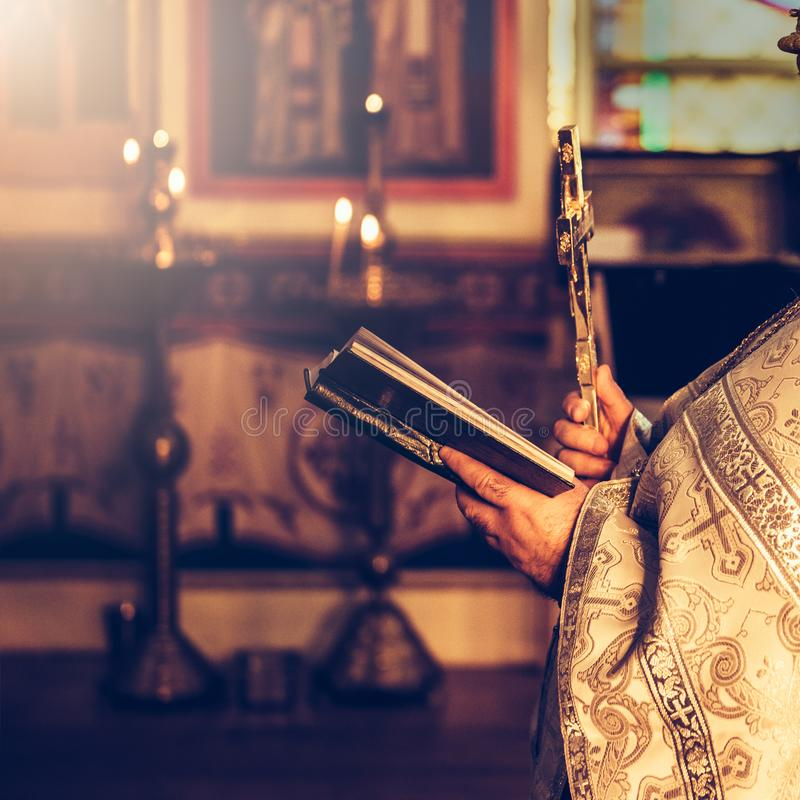 Priest praying in the church holding holly bible and cross.  royalty free stock image