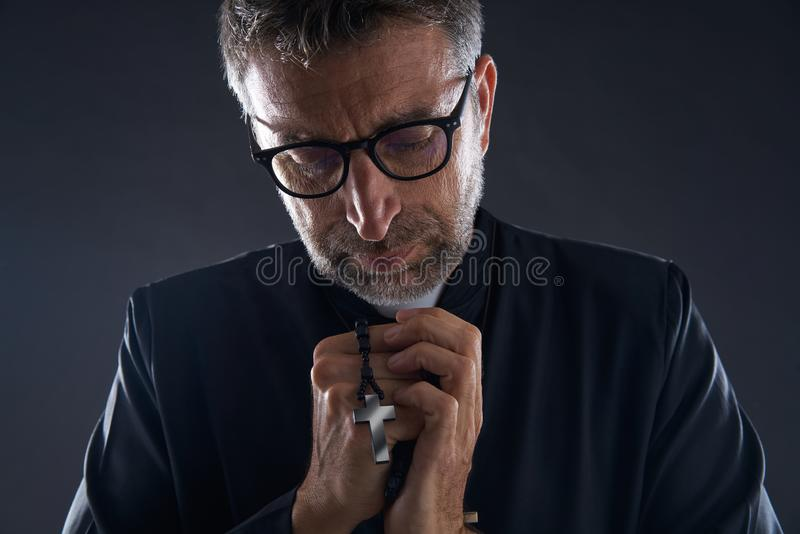 Priest praying hands with rosary beads stock photo
