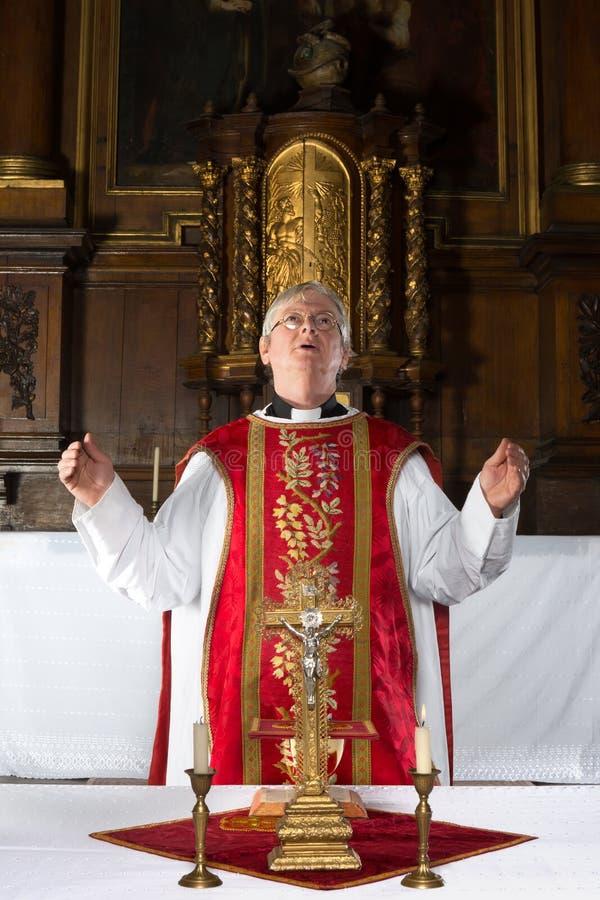 Priest praying during mass royalty free stock image