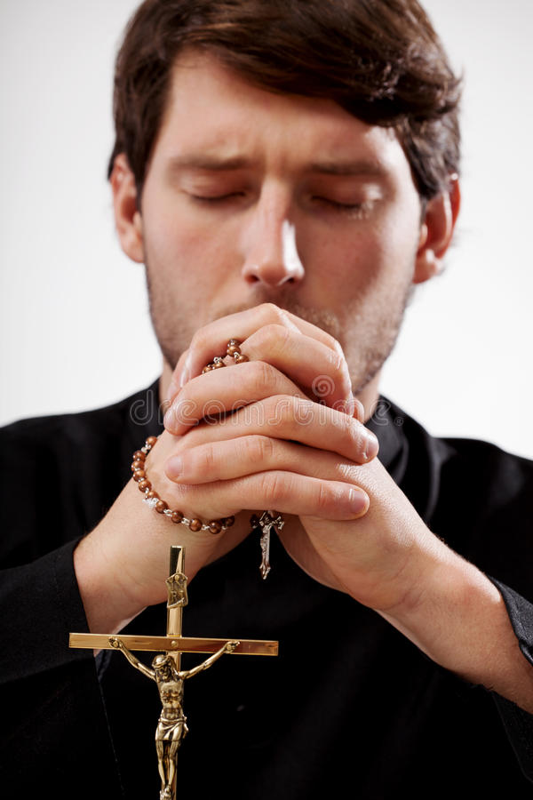 Priest is praying the rosary royalty free stock image
