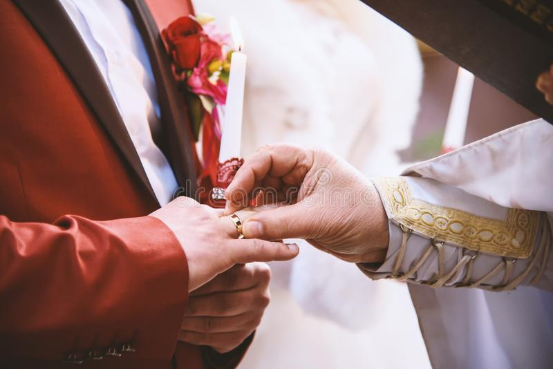 Priest putting wedding ring on the grooms finger, marriage vow, Christian traditions. Priest put wedding ring on grooms finger, marriage vow, Christian royalty free stock images
