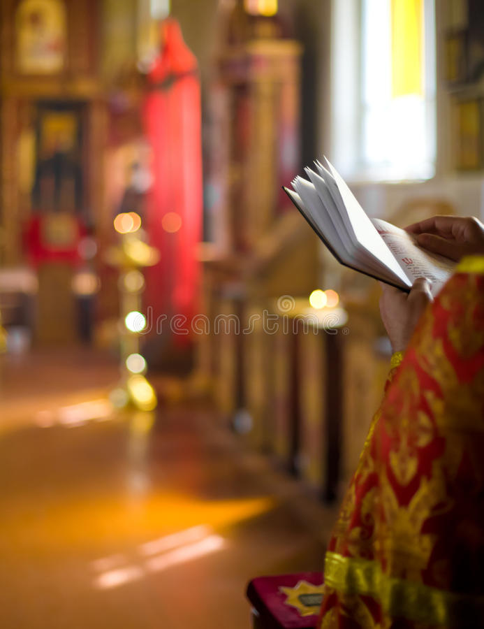 Priest reading Bible in Orthodox church interior stock images