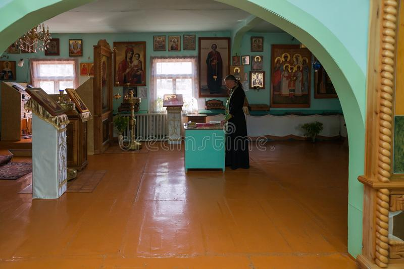 The priest reads a prayer in front of the altar in the interior of the village Russian church stock photos