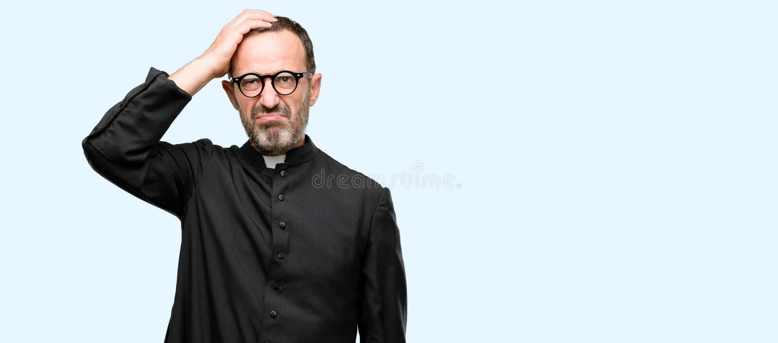 Handsome senior man isolated over blue background. Priest religion man doubt expression, confuse and wonder concept, uncertain future isolated over blue royalty free stock images